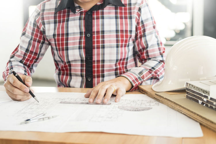 Midsection of engineer working on blueprint while sitting at table