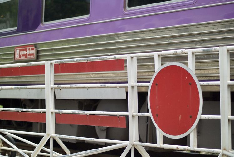 Close-up of metal barricade by train