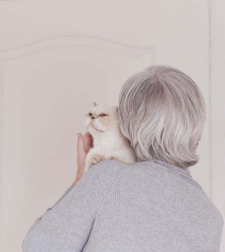 Rear view of woman with cat