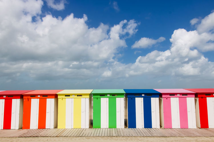 Multi colored beach huts against cloudy sky