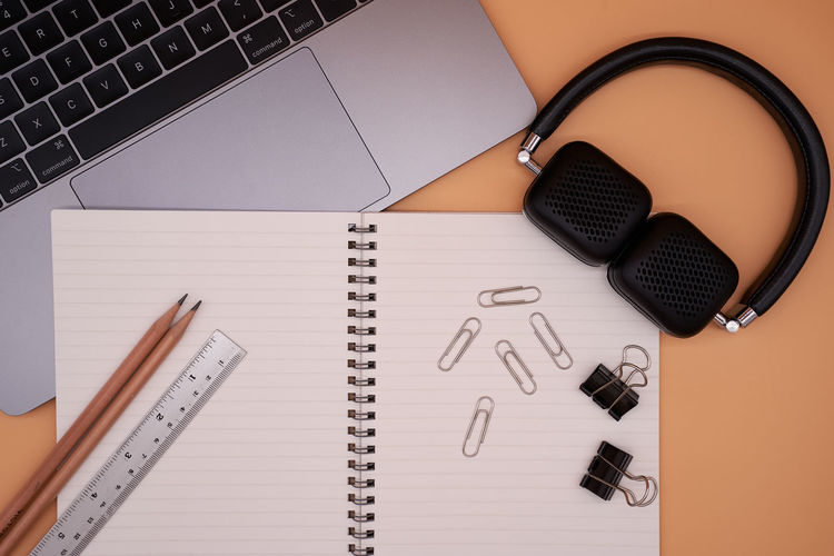 Directly above shot of laptop with office supplies and headphones on brown background