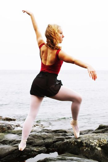 Full length of ballet dancer practicing on rocks at beach against clear sky