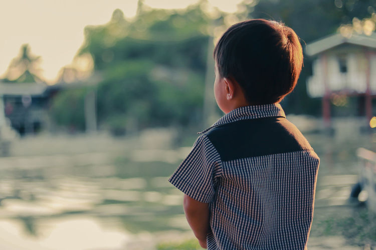 Rear view of boy standing against lake during sunset