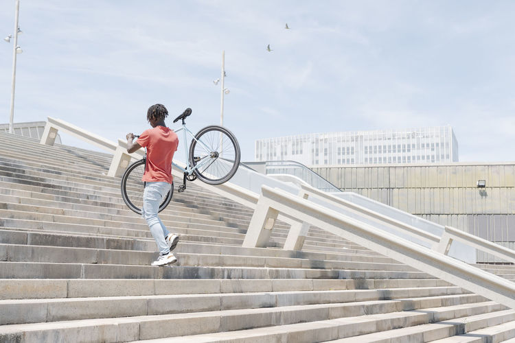 Full length of boy on staircase in city against sky