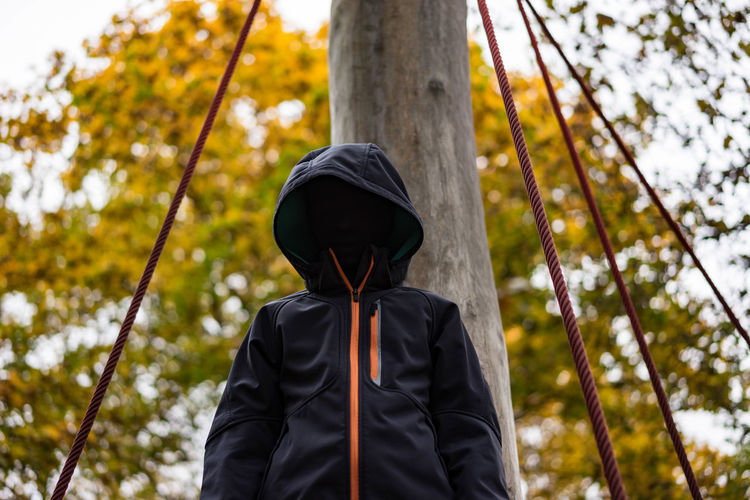 Low angle view of boy wearing hooded shirt against pole