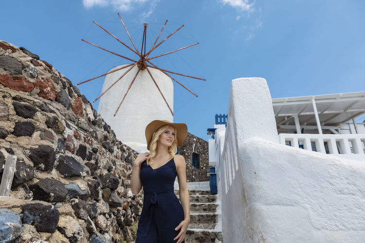Smiling woman in hat against traditional windmill