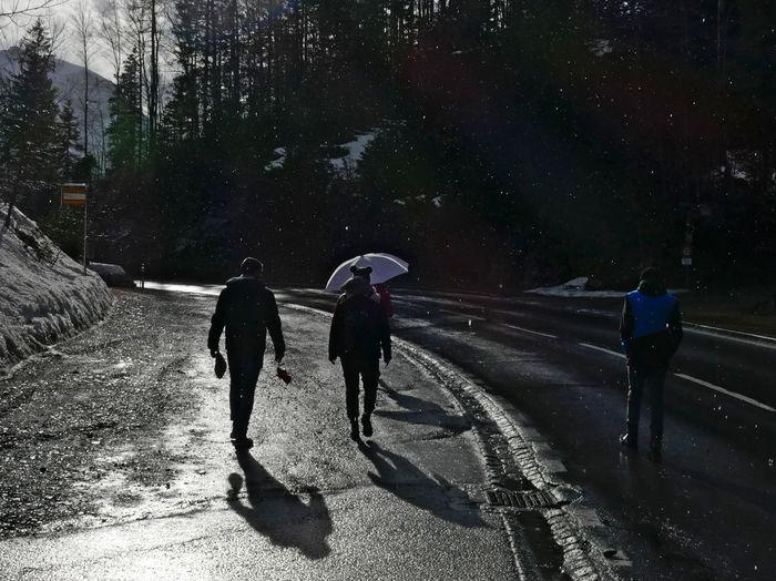 Rear view of people walking on road in rain