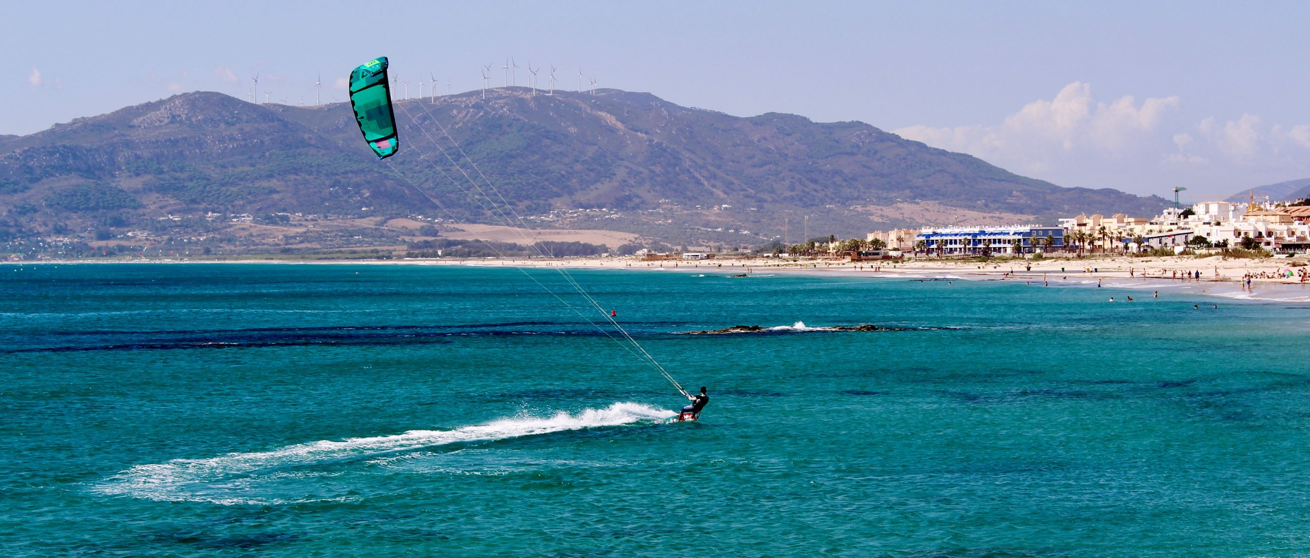 water, sport, sea, mountain, extreme sports, aquatic sport, leisure activity, beauty in nature, waterfront, real people, lifestyles, adventure, motion, one person, surfing, nature, sky, day, scenics - nature, kiteboarding, skill, outdoors, turquoise colored