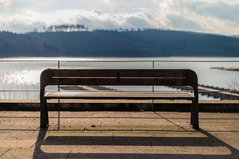 Empty bench by river against sky