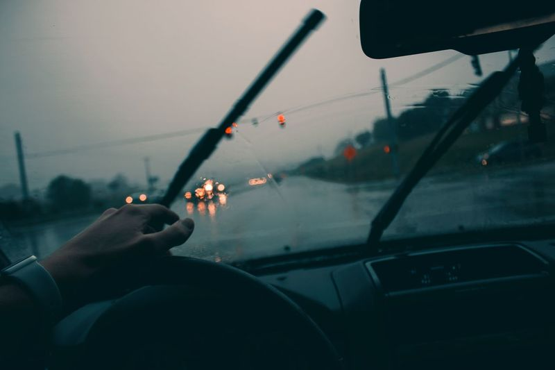 Cropped hand driving car during rainy season