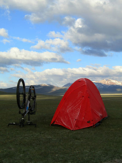 Bike & tent in early morning at Song Kol Lake in Kyrgyzstan. Grass Kyrgyzstan Red Adventure Beauty In Nature Bicycle Bike Camping Cloud - Sky Clouds Day Early Morning Field Grass Landscape Mountain Nature No People Outdoors Red Scenics Sky Tent