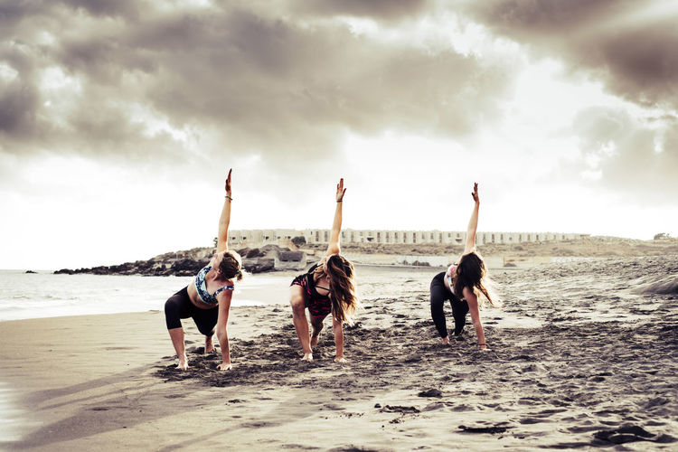 Women doing stretching at beach against sky suring sunset