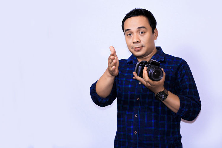 Portrait young Asian Photographer One Person Front View Studio Shot Standing Waist Up Young Adult Indoors  Copy Space Looking At Camera White Background Holding Casual Clothing Portrait Young Men Men Cut Out Gesturing Technology