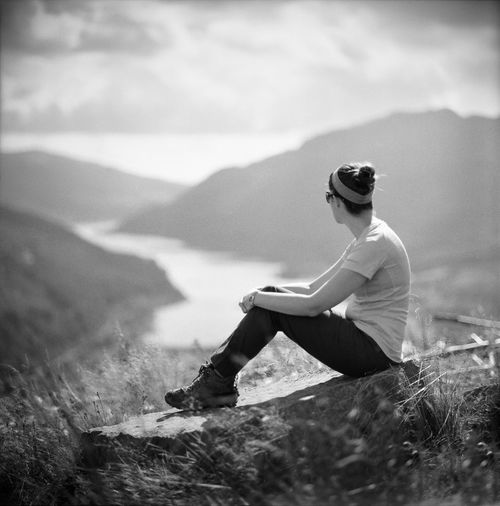 Side view of woman sitting on rock at cliff against valley