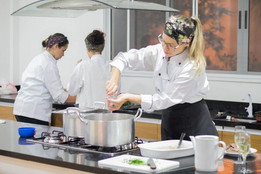 Adult Adults Only Chef Chef's Whites Commercial Kitchen Cooperation Day Expertise Food And Drink Establishment Indoors  Looking Down Men Occupation People Preparation  Preparing Food Protective Workwear Restaurant Skill  Stove Uniform Women Working Young Adult Young Women