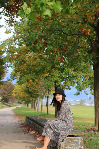Portrait of woman standing by tree