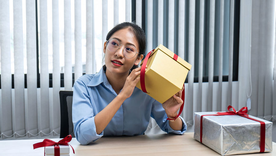 Portrait of woman sitting in box on table
