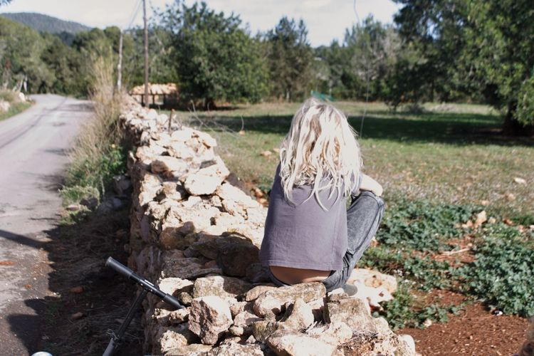 Rear view of girl sitting on stones against trees