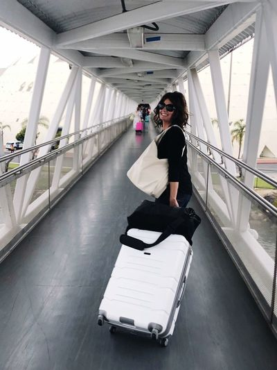A woman traveling through a terminal to a cruise line with her white large suitcase on wheels, wearing sunglasses and smiling for the camera before she enters the ship. One Person Carrying Luggage Vacation Destination Vacationdays Vacation Entering Cruise Via Terminal Suitcase On Wheels White Suitcase Woman With Suitcase Vacation Time Cruise Terminal Terminal Station Terminal Building Full Length Architecture Transportation One Person Young Adult Lifestyles Women Adult Looking At Camera Day Connection Young Women Portrait Outdoors Real People Built Structure