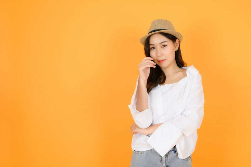 Young woman looking away while standing against orange background