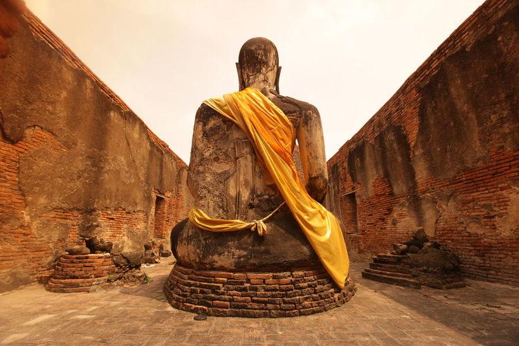 Buddha statue amidst wall at ayutthaya kingdom against clear sky