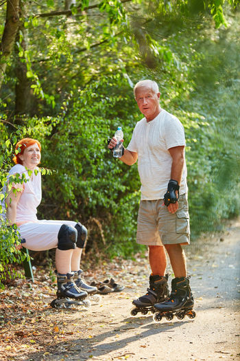 full length of man holding umbrella against trees Active Adult Bottle Casual Clothing Couple Day Drink Environment Family Fitness Forest Full Length Happy Hobby Holding Inline Inline Skates Inline Skating Leisure Leisure Activity Lifestyles Males  Man Men Movement Nature Old Outdoors Outside People Plant Real People Refreshment Rollerblades Roller-skates Senior Senior Adult Senior Citizen  Senior Citizens Senior Men Seniors Skater Skates Smiling Sport Summer Thirsty  Together Togetherness Tree Two People Vital Water