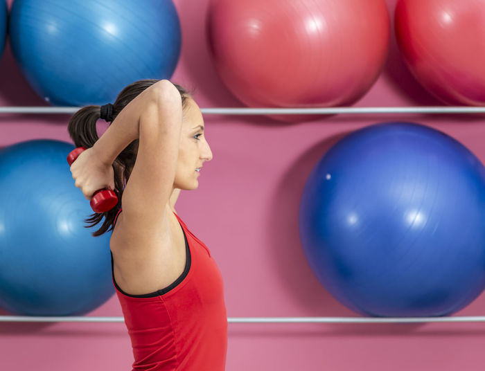 Side view of woman lifting dumbbell against fitness balls