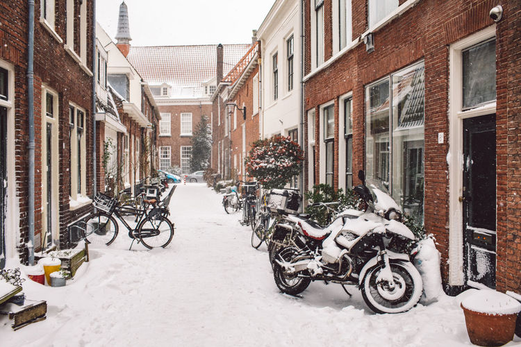 Bicycles parked on street amidst buildings during winter