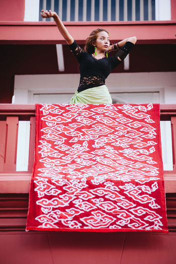 Woman standing in balcony at railing
