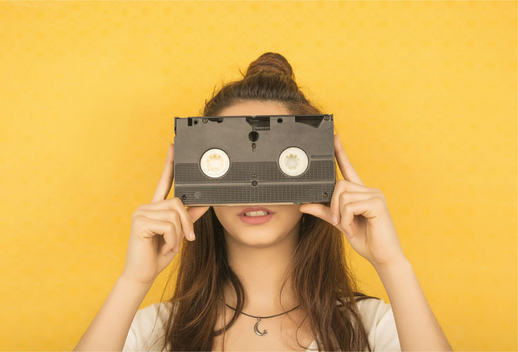 Woman Holding Audio Cassette Against Yellow Background