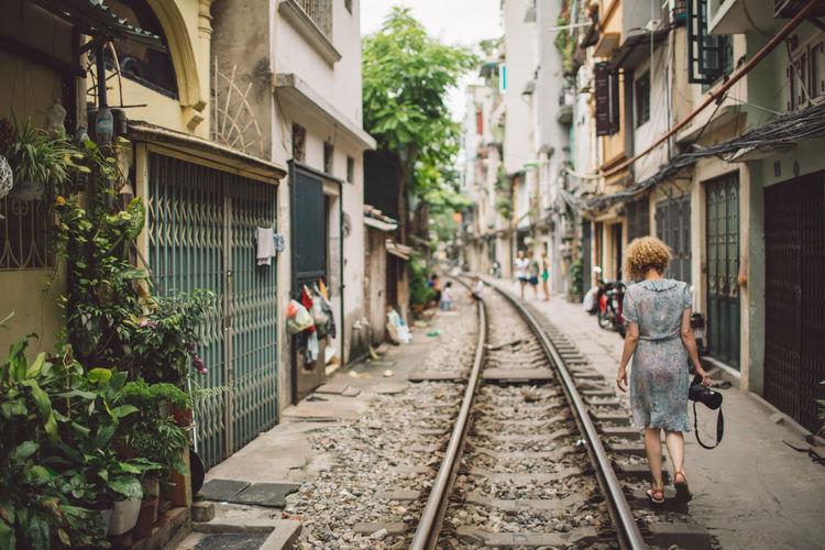 Woman walking on railroad track in city