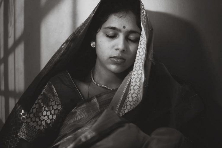 Close-up of woman with eyes closed in traditional clothing against wall