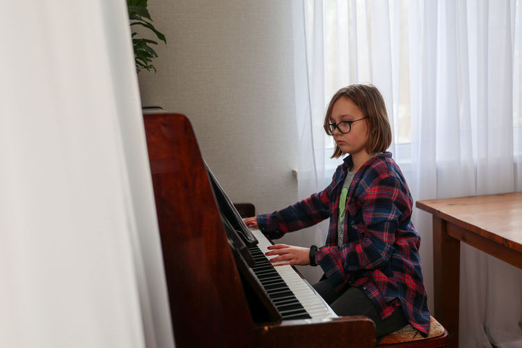 Side view of young woman playing piano at home