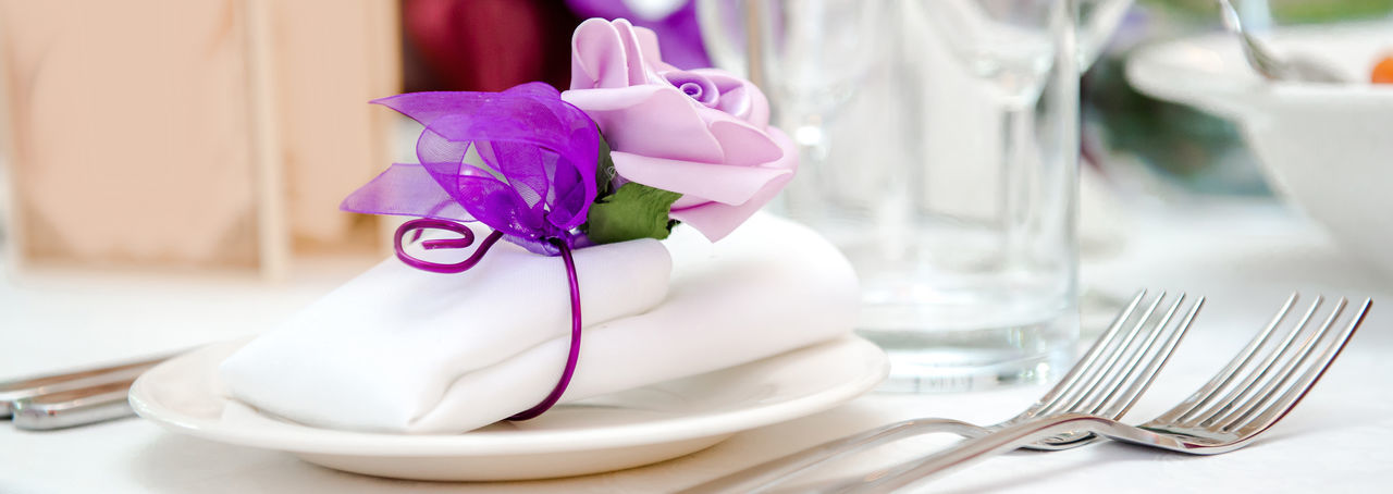 Banquet Table Restaurant Decoration Decor Arrangement Setting Table Appointments Flower Violet Purple Pink Folded Napkin White Glass Crockery Fork Utensil Plates Dish Dishware Event Wedding Holiday Celebrate Celebration Party Luxury Luxurious Elegant Closeup Dishware Nobody Serving Catering Indoors  Cutlery Reception Drink Tablecloth Romantic Tasteful Beautiful Beauty Panoramic Panorama Horizontal Banner Design Background Header