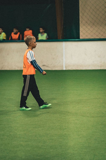 Sport Real People Leisure Activity One Person Ball Lifestyles Soccer Side View Full Length Child Childhood Men Green Color Sports Equipment Athlete Motion Indoors