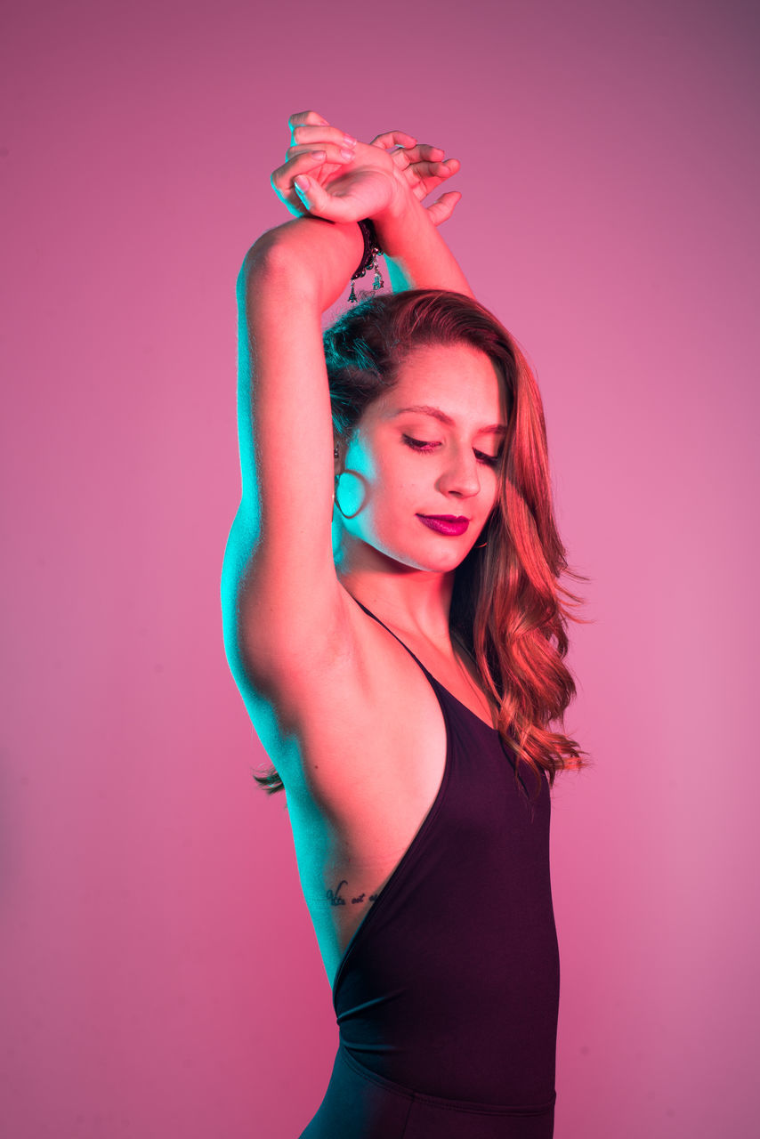 Sensuous Young Woman Standing Against Pink Background