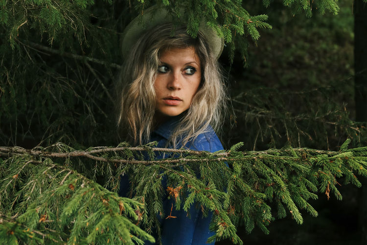 The girl in the blue dress behind the branches of the fir