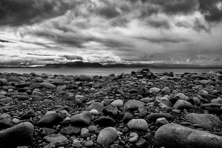 Scenic view of rocky beach against cloudy sky