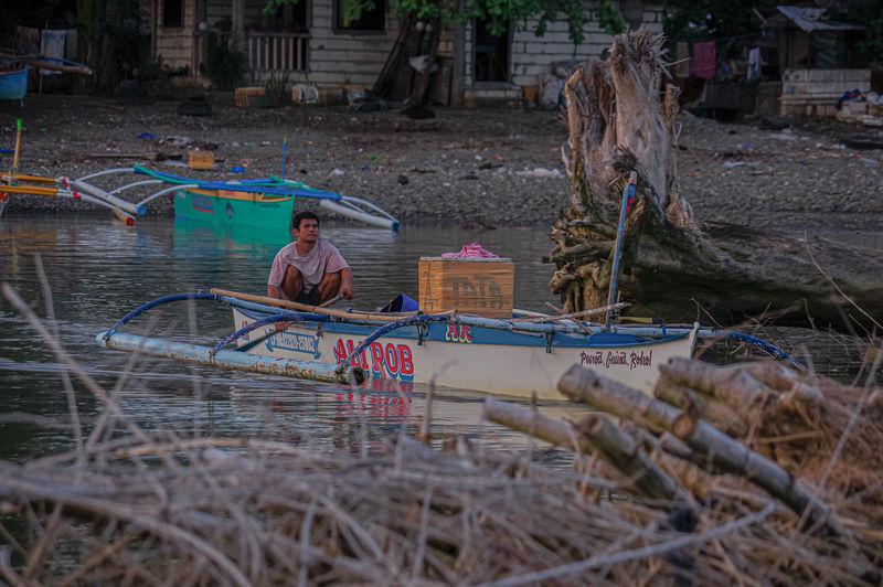 Man sitting by fishing rod on land