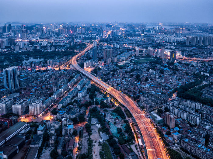 Aerial view of bridge amidst cityscape at dusk