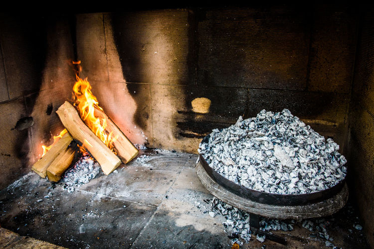 Cooking of traditional Balkan Greek Mediterranean Croatian meal Peka in metal pots called sac sach or sache or a metal lid. Fireplace with open fire and burning coals. BBQ Balkan Croatia Metal Pot Barbecue Barbecue Grill Charcoal Coal Coals Fire Fireplace Food Grill Lid Meat Metal Octopus Outdoors Peka Preparing Preparing Food Restaurant Roast Sache Traditional
