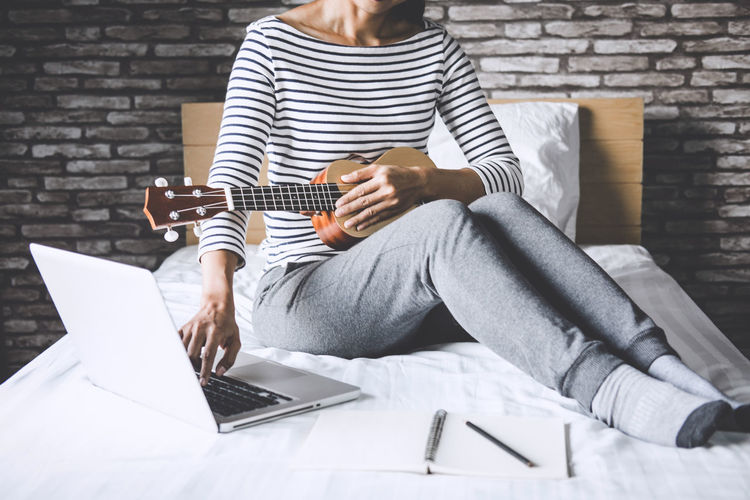 Low section of woman with guitar using laptop while sitting on bed