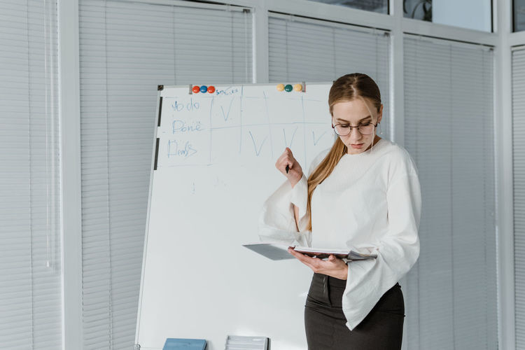Businesswoman reading diary while standing by whiteboard in office