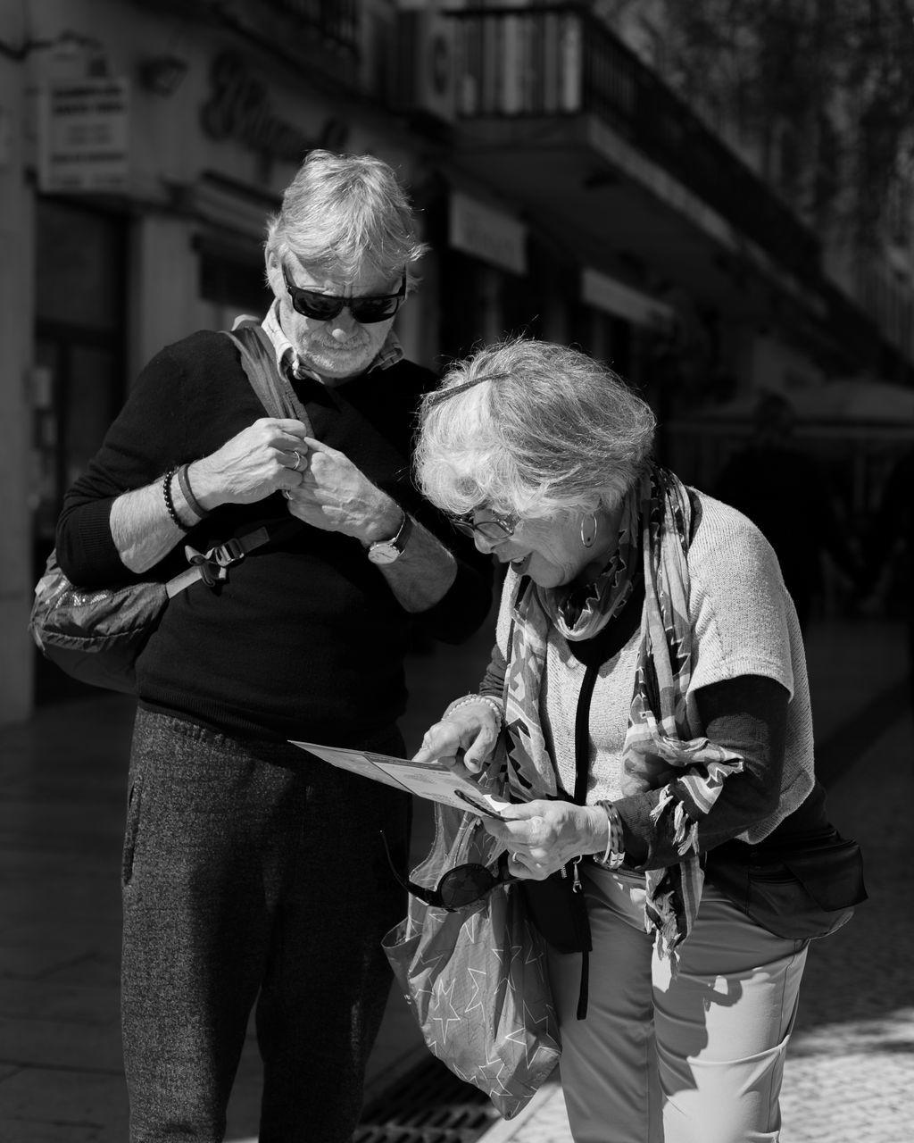 WOMAN HOLDING UMBRELLA ON SIDEWALK