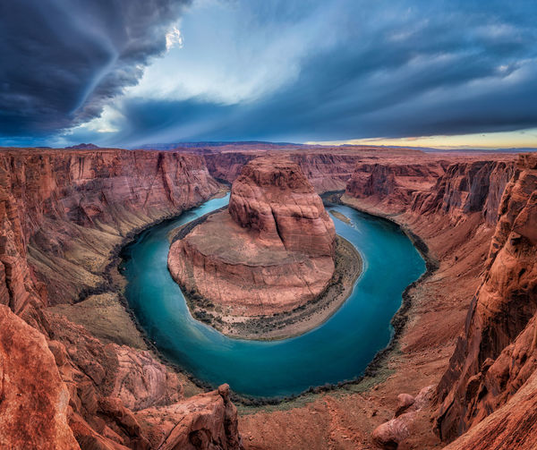 Scenic View Of Horseshoe Bend Against Cloudy Sky