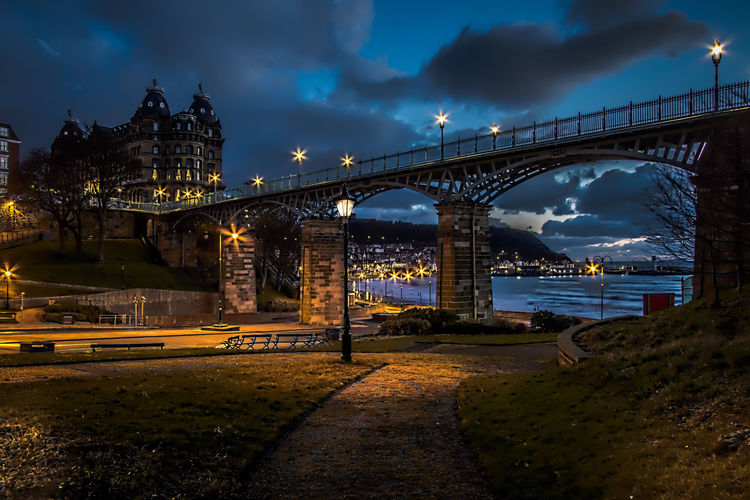 Illuminated bridge over street at scarborough against sky