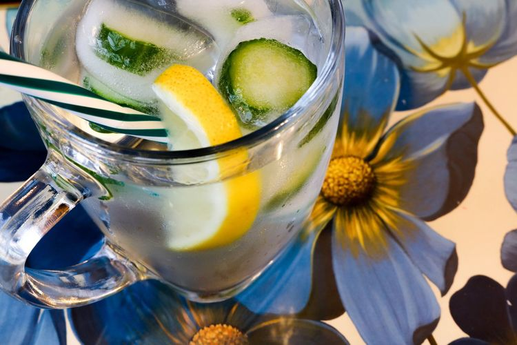 Drink with cucumber ice cubes and lemon with a blue flower background Day Indoors  Close-up No People Freshness Food And Drink Refreshment Drink Drinking Glass EyeEm Selects Water Cold Drink Ice Cubes Lemon Slice Drinking Straw Blue Flowers Trays