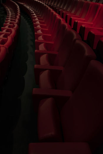 Movie Theater. Red Indoors  In A Row No People Close-up Seat Movie Theater Arts Culture And Entertainment Repetition Auditorium Empty Film Industry Pattern Chair Dark Absence Order Arrangement Relaxation Large Group Of Objects Side By Side Spot Light  Illuminated Abundance Cinema