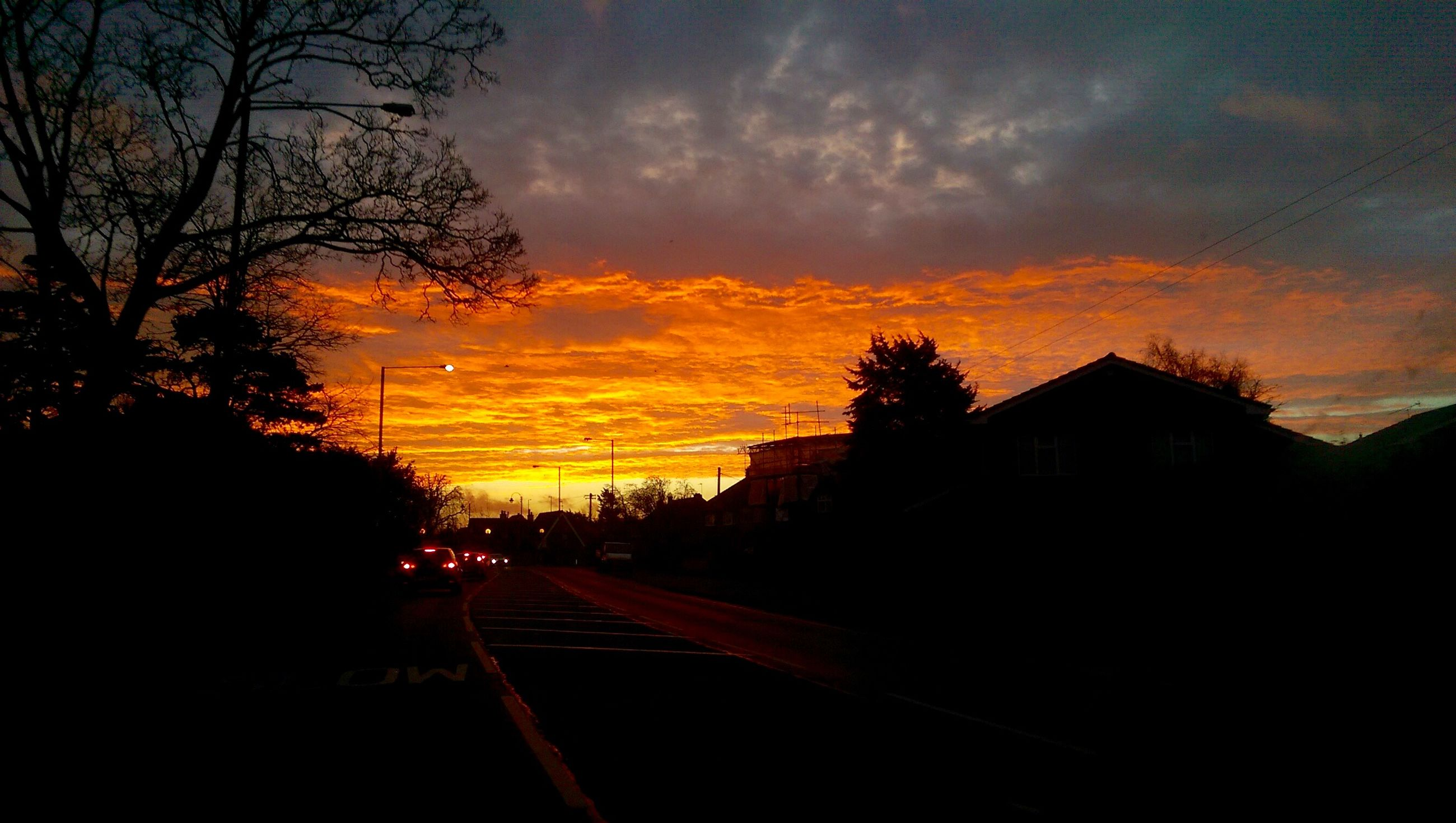 sunset, sky, transportation, silhouette, cloud - sky, tree, orange color, building exterior, the way forward, road, built structure, architecture, cloud, street, dusk, car, bare tree, dramatic sky, house, cloudy