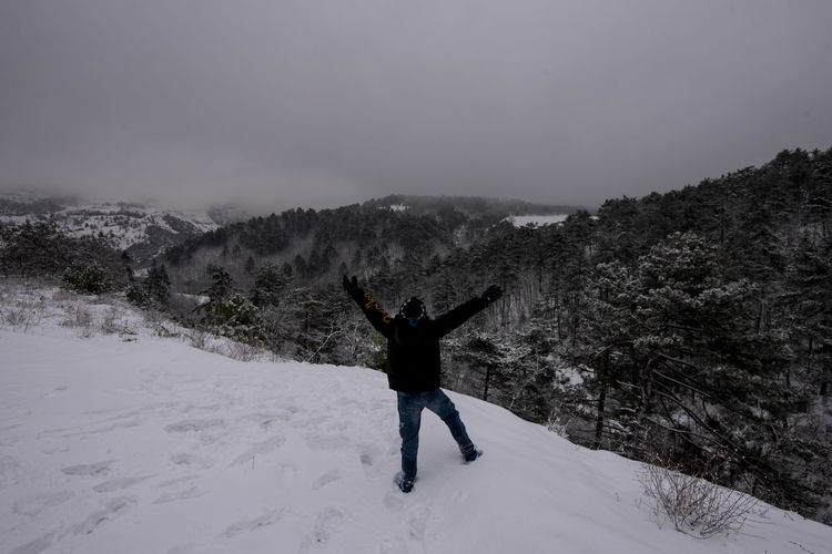 Snow Winter Cold Temperature One Person Beauty In Nature Sky Leisure Activity Real People Mountain Rear View Adventure Human Arm Lifestyles Scenics - Nature Nature Holiday Vacations Limb Arms Outstretched Mountain Range Warm Clothing Arms Raised Outdoors